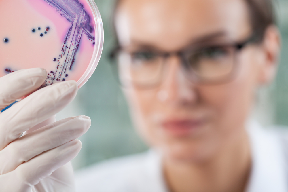 Microbiologist holding a Petri dish with bacteria, horizontal